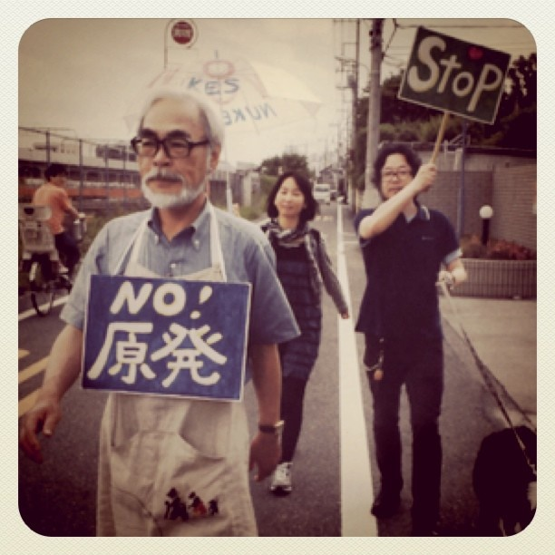 Hayao Miyazaki marching to protest against nukes, with 2 people and 1 dog
