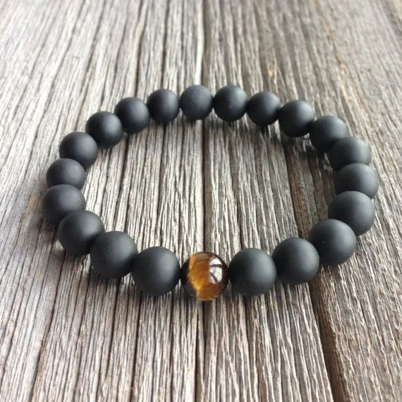 ONYX AND TIGER EYE MEN'S BEADED BRACELET | By purchasing this bracelet, you will fund the removal of 20 pieces of plastic from the ocean and coastlines. Handmade and fairly traded. Onyx beaded bracelet accented with a single tigers eye bead. Onyx is a stone of centering, self-control, and intuitive guidance. While the tiger's eye promotes optimism and intuition