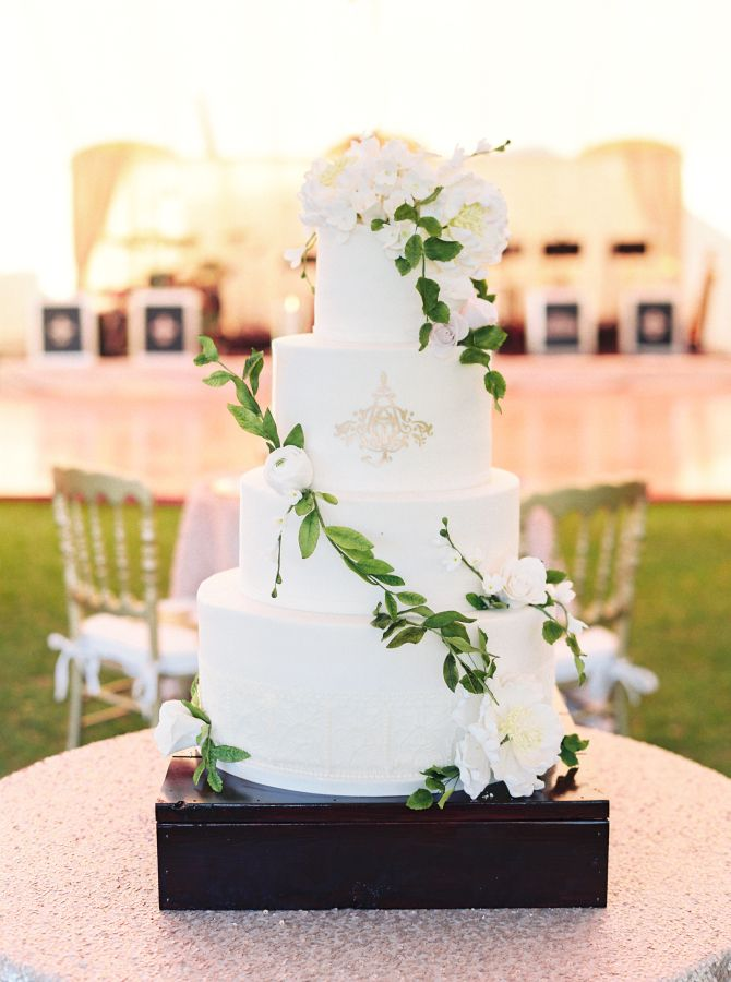 Four tier wedding cake topped with ivory florals: http://www.stylemepretty.com/2017/01/17/the-wedding-of-ana-cristina-cash-john-carter-cash-son-of-june-carter-johnny-cash/ Photography: Perry Vaile - http://www.perryvaile.com/
