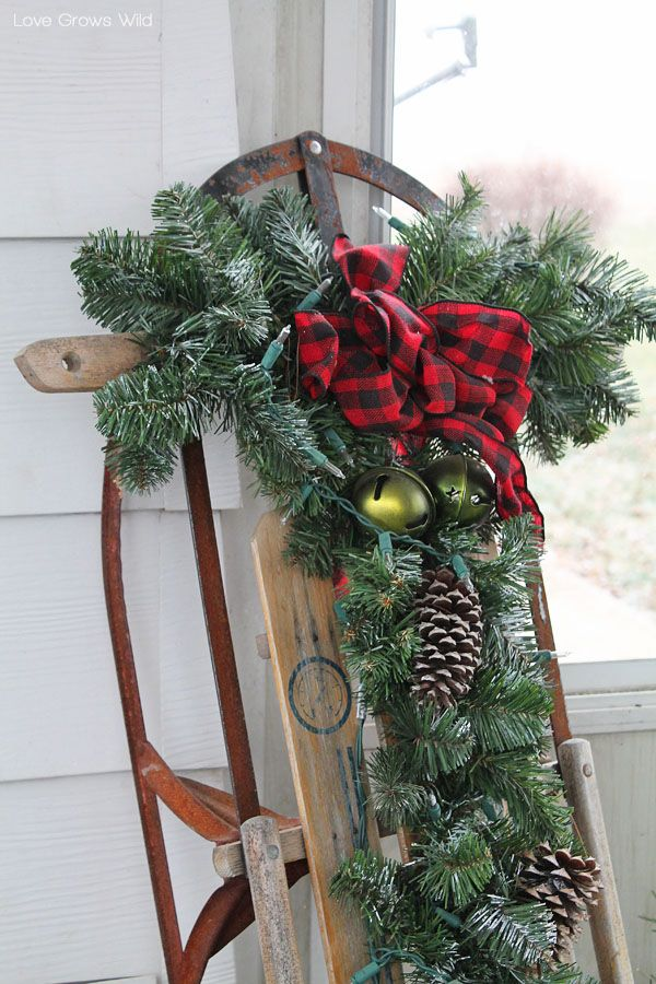 Add some holiday accessories such as pinecones, bells, lights, and greenery to a vintage snow sled to decorate for winter!