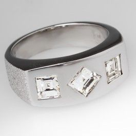 This retro gents ring is crafted of solid 14k white gold and features three flush set square step diamonds.  The diamonds total 1.35 carats and the ring is a hefty 10.8 grams.  This retro mens ring has a nice bright smooth polish with contrasting textured shoulders which make it very visually appealing.