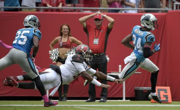 Carolina Panthers cornerback Josh Norman (24) runs 46-yards for a touchdown after intercepting a pass by Tampa Bay Buccaneers quarterback Jameis Winston (3) during the first quarter of a game Sunday, Oct. 4, 2015, in Tampa, Fla. Panthers' Bene' Benwikere (25) blocks Winston.