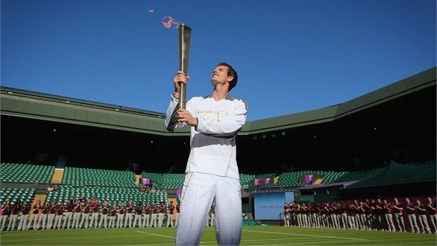 Britain's Andy Murray holds the #OlympicFlame on Centre Court at #Wimbledon on Day 66 of the Olympic Torch Relay.