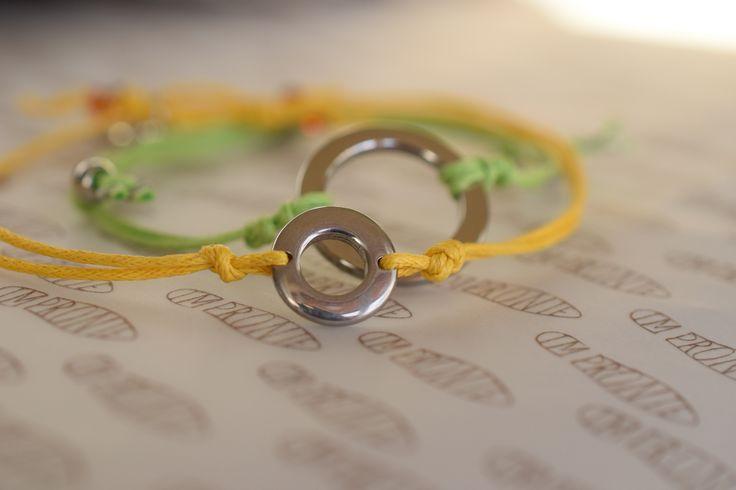 Náramek navlečen na barevné šňůrce, zelené nebo žluté barvy, zapínání zdrhovací, s komponentem kruh z chirurgické oceli ve dvou velikostech,1 a 2 cm, s ozdobnými konci a medailonkem Impronte.