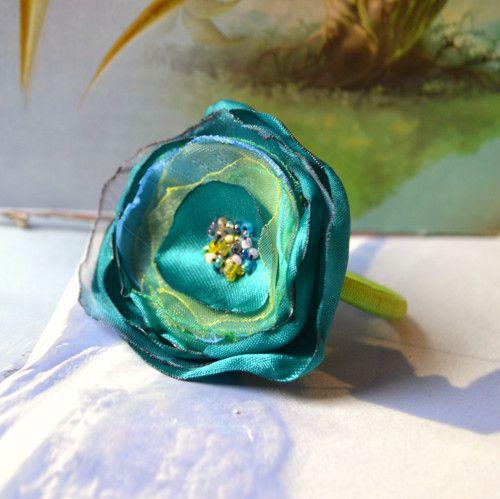 Gumička do vlasů je vhodná pro každou příležitost. Květinka je vyrobena ze saténu a organzy,  střed je vyšitý korálků.  Ozdobte si účes krásným romantickým kvítkem na gumičce.  Rozměry kvítku: 5,5 cm (průměr)  Barva gumičky: zelená