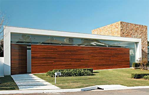 A fachada chama a atenção pela bem-sucedida mistura de materiais: o longo painel de freijó no qual está inserida a porta de entrada, o rasgo...