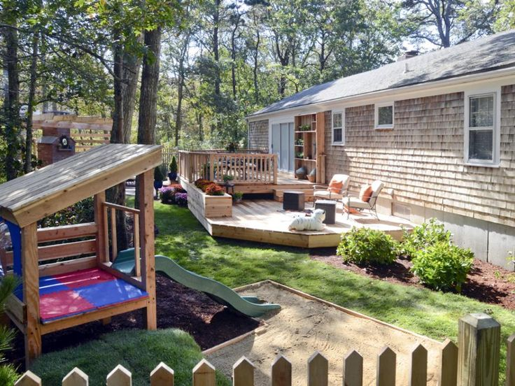 This family-friendly backyard includes entertainment for adults and kids alike. A playground with a small slide provides entertainment for the little ones, while a two-level deck creates enough space for outdoor dinner parties for adults.