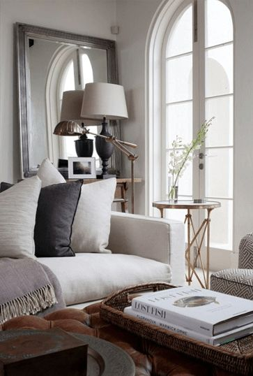 Amazing design by Coco Republic; white sofa, brown leather tufted ottoman, subtle but graphic chairs, and gold side tables to boot.