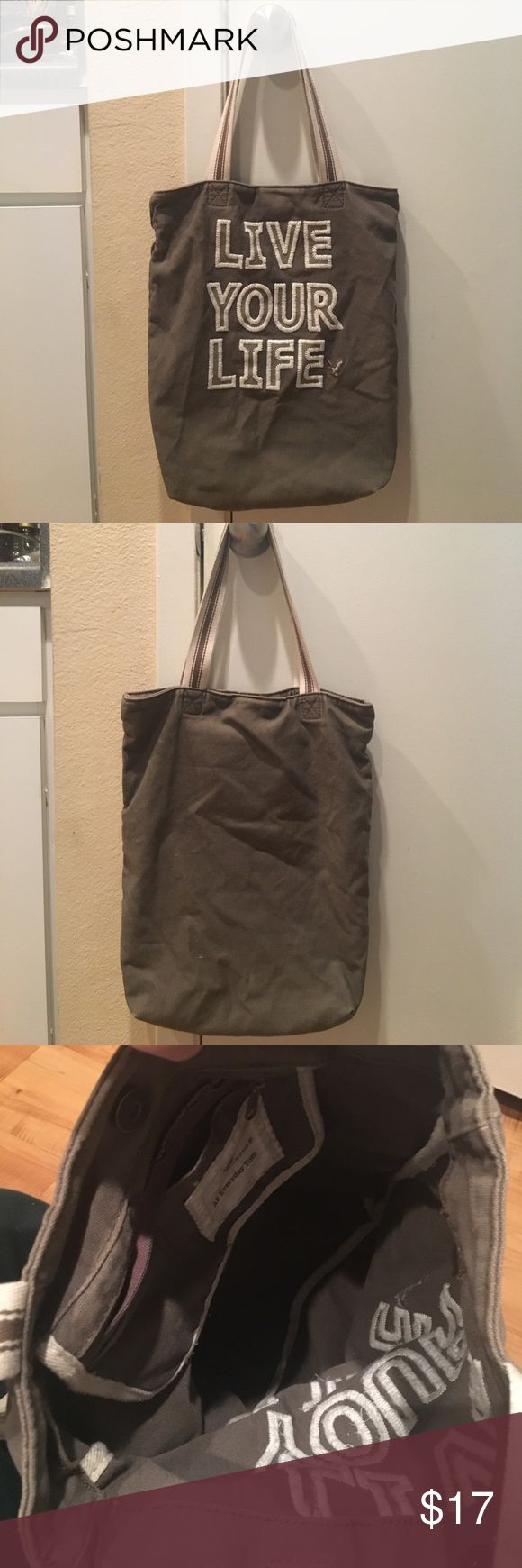 """American Eagle Everyday Tote Great for throwing books in and heading to class. Grey/Army Greenish color. Magnet closure at top. Internal pocket with zipper. A couple slight use marks (see pic) on front and back. Still in great shape. About 14"""" wide x about 16"""" long. Canvas. Sewn detail around lettering. American Eagle Outfitters Bags Totes"""