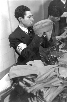 A Jewish worker wearing an armband, is holding one of the berets he produced. Warsaw, Poland, 1941, A workshop for sewing German Army berets.