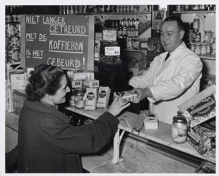 Kruidenier met bord op toonbank 'Niet langer getreurd, met de koffiebon is het gebeurd!' (Door de fotograaf geënsceneerde foto), 1951.