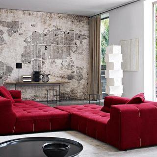 Sala de estar com parede de jornal e sofá vermelho