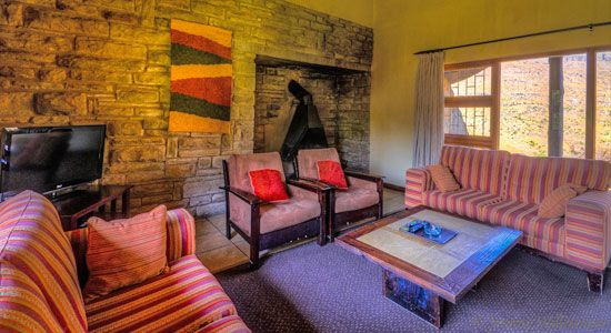 Lounge with fireplace in the self-catering 6 bed cottage at Thendele Camp in the Royal Natal Park located in Northern Drakensberg, KwaZulu-Natal
