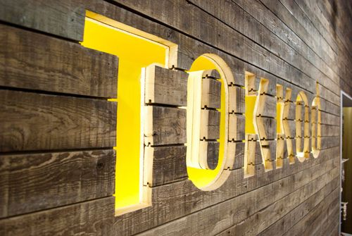 TOKKAD | type routed out of wood planks, lit with neon #color