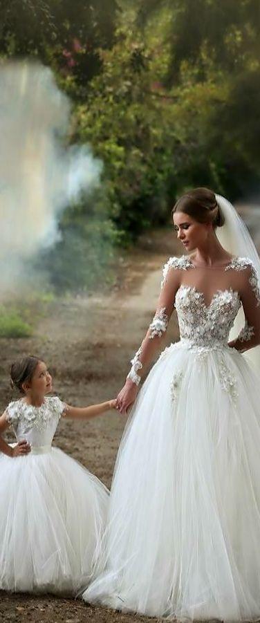 Vestido de noiva no estilo princesa, com transparências que fazem com que pareça que a renda está colocada diretamente na pele da noiva. O penteado, o véu e a daminha também estão lindos!