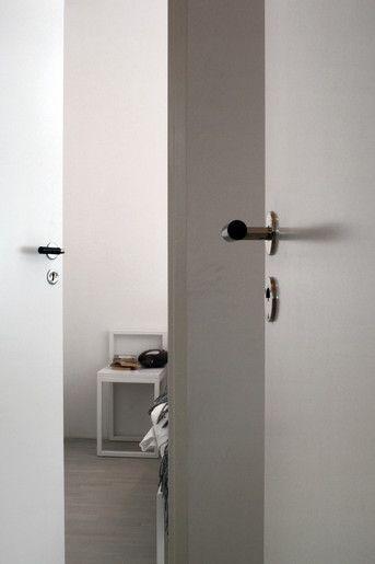 Enkla, släta dörrar i ett hem i minimalistisk stil i västra hamnen i Malmö. Funkisdörrhandtagen förstärker de rena formerna. Vitoljade furugolv i rummen.