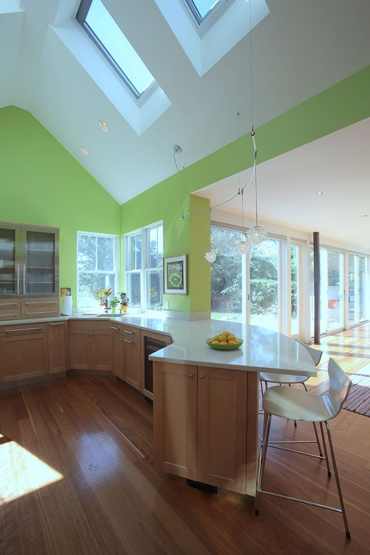 modern kitchen with curved counter skylights green walls bar seating cape cod home