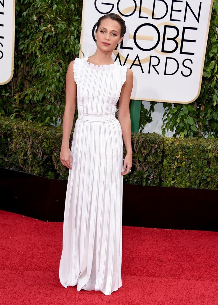 """Actress Alicia Vikander, a double nominee for her performances in """"The Danish Girl"""" and """"Ex Machina,"""" struck a pose on the red carpet in a pleated white Louis Vuitton dress. The actress made her first awards-show appearance with boyfriend Michael Fassbender -- the two sat together during the show on Jan. 10, 2016."""