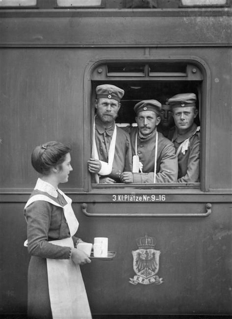 1915 WWI soldiers at a station being helped by volunteer woman