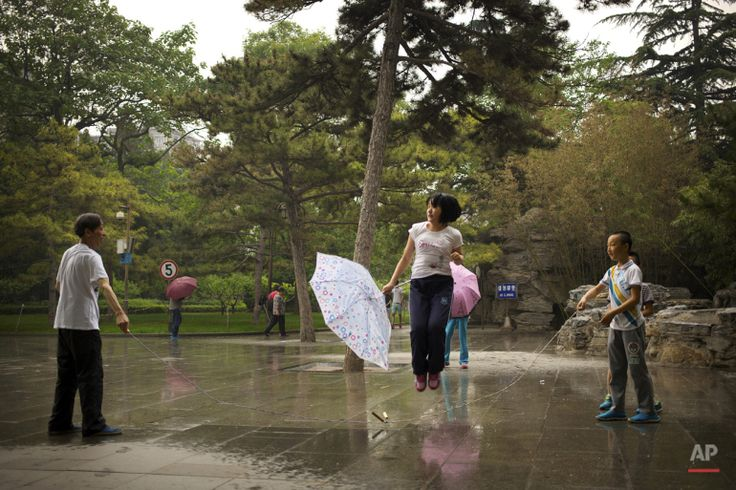 In this Sunday, May 17, 2015 photo, a girl holds an umbrella as she skips rope during a rain shower at a park in Beijing. (AP Photo/Mark Schiefelbein)