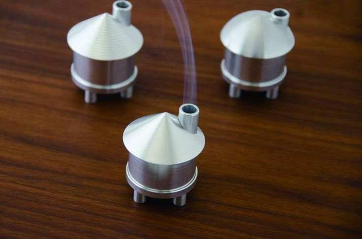 The Aroma House takes it to a sparse modernist level. Crafted in silver brushed-alloy, it looks like a cylindric engine part topped with either a conical or domed roof that sports a chimney to release the incense smoke.