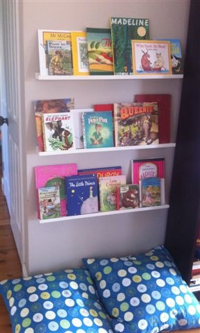 Great way to make a place for all the kids books. Love the pillows underneath too.