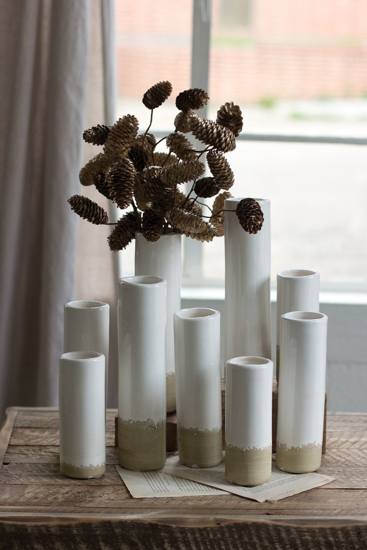 Dipped in a soothing white ceramic glaze, this set of bud vases feature a raw…