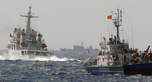 Esta imagen tomada de un barco de la Guardia Costera de Vietnam el 14 de mayo de 2014, muestra un barco de la Guardia Costera de China (L) bloqueando el paso de un buque de la Guardia Costera de Vietnam cerca del sitio de una plataforma petrolera de perforación china (R, fondo) siendo instalado en el agua en disputa en el Mar del Sur de China frente a la costa central de Vietnam. (Hoang Dinh Nam / AFP / Getty Images)