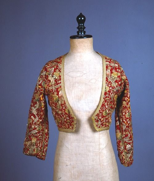 Kondogoúni, jacket made from a Turkish anderí for the 'Amalia' costume Peloponnese. Mid 19th century H. 0.34 m. © Peloponnesian Folklore Foundation, Nafplion, Greece The kondogoúni is made of red cotton, embroidered all over with gold thread and spangles in floral designs. All the openings are edged with braid and the lining is purple. It was remade from an Turkish anderí.