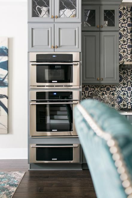 """A 30"""" electric single wall oven with wave touch controls is paired with a built-in convection microwave with drop-down door. The two ovens are joined by a 30"""" warming drawer below."""