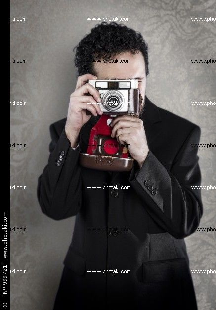 http://www.photaki.com/picture-photographer-with-black-suit-on-vintage-background-with-old-camera_999721.htm