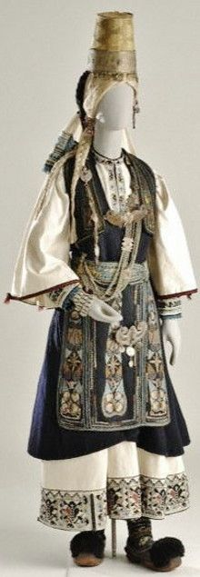 Bridal costume of the Pindus-mountain Nomads was worn by the Arvanitovlachs (Albanian-Vlachs) called the Karagounides of Epirus. It consists of a white chemise with embroidery at the hem and bib, a black segouni (sleeveless coat) and a woven apron. Additional human hair braids are fastened to the hair, and the headdress consists of a tall cone-shaped hat with a silver band around its base as a diadem. Silver chains on the chest, a buckled belt (the kemeri) and bracelets complete the costume.