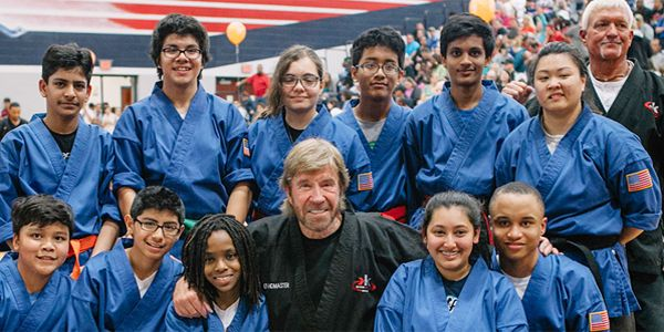Chuck Norris (center) with children of Kickstart Kids