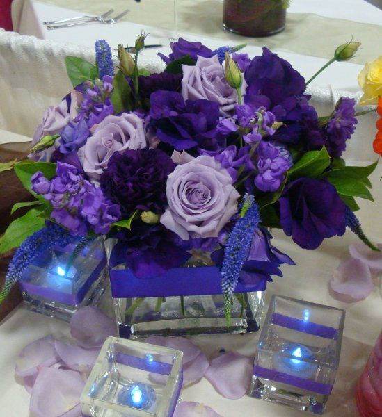 square vase with purple ribbon, light purple roses, dark purple lisanthus, carnations and purple stock, flower centerpiece.