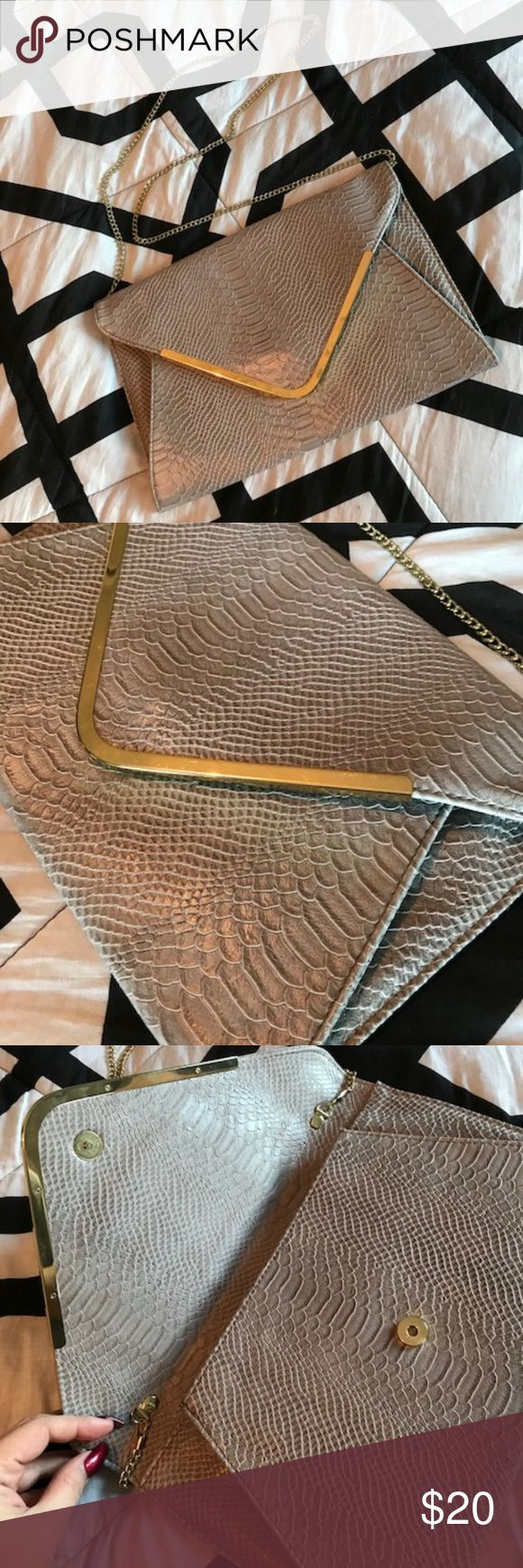 "Steve Madden grey faux snake skin clutch crossbody HOT! Steve Madden grey faux snake skin clutch sheens slightly purple in the sun.  Gold toned hardware and removal chain to go from shoulder purse/crossbody to clutch.  EXCELLENT condition, no blemishes! Interior is clean and has two pouches on one side and zipper compartment on the other.  Back has Steve Madden gold toned plate.  Snap closure. Smoke Free/Pet Free. 14"" length 9"" height .25 inches width 22"" shoulder drop  Offers Are Welcomed…"