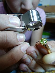 Close-up of a jeweller looking at a green and gold ring through a magnifying glass THIS IS ACTUALLY MY ENGAGEMENT RING :)