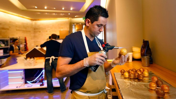 Christophe Rull, executive pastry chef at the Park Hyatt Aviara in Carlsbad, uses a blow torch to smooth the surface of golden sugar ornaments.