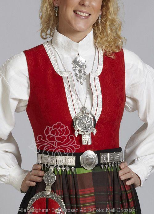 Nordmørsbunad med rødt liv, sort stakk, rutete forkle, skjorte med labbsøm og tett sølvbelte.