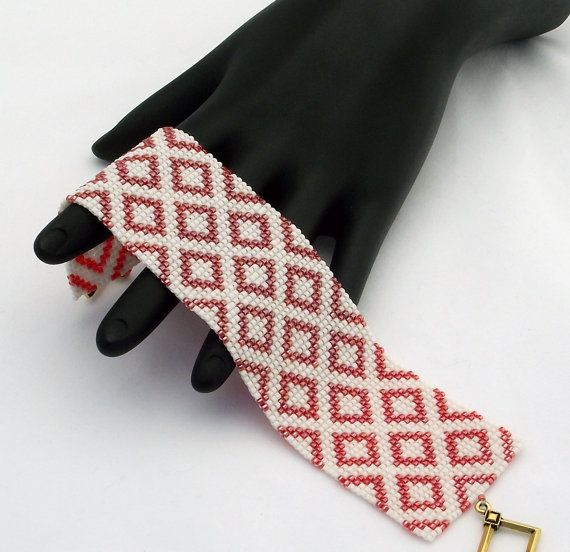 Questo braccialetto caratteristiche diamanti di perline delica rosso fragola trasparente su un mascherino arrossito sfondo bianco. Il braccialetto è rifinito con una chiusura di peltro placcato oro antica.  Questi braccialetti di farsi notare. Ogni perlina in questo pezzo viene cucita individualmente per un prodotto finito che si comporta come un pezzo di tessuto ed è altrettanto comodo da indossare.  • Larghezza - 38mm o 1,5 • Lunghezza compreso chiusura - 192mm o 7,6 • Chiusura - anello…