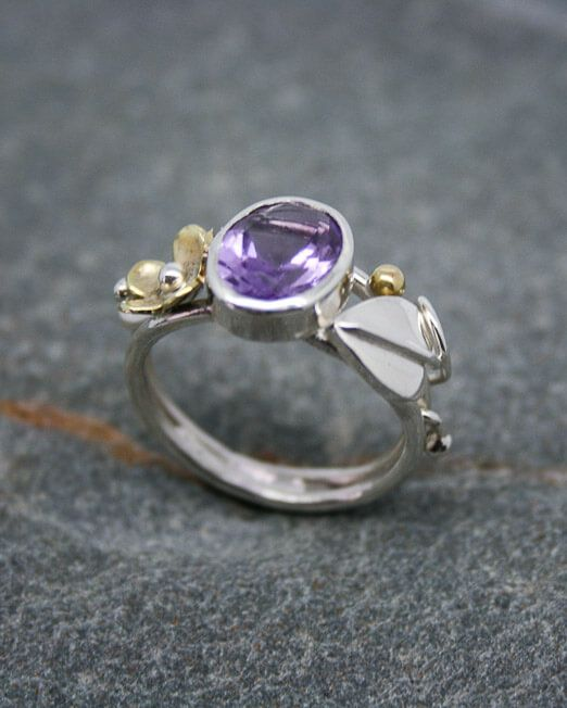 A unique, handmade art nouveau styled silver ring with amethyst.  The amethyst is an oval facetted 10mm. x 8 mm. and bezel set. To one side is a single brass daisy with silver bead and stem, to the other side is a single silver leaf with entwined stem wrapping around the shoulders, creating this very natural feel.  From our unique collection of mixed metal jewellery created here in our own...