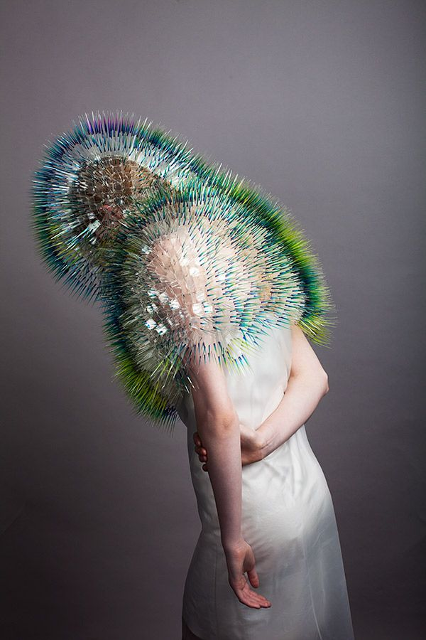 Maiko Takeda rchitectural headpieces resemble porcupine quills, ostrich feathers and tiny iridescent fish scales, all artfully woven together with logic and geometry in mind. Their likeness to elements of the natural world are apt, too, as the pieces react strongly to the light, wind and colours of the environment they are worn in.