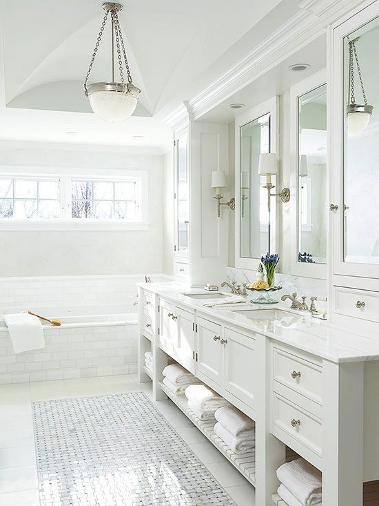 White-on-white isn't for everyone, but you have to agree, the results can be quite stunning. In this elegant bathroom, a mix of sheens and details bring a monochromatic white palette to life. Glossy tilework and mirrored surfaces contrast the matte finish on the cabinetry and walls. Fluted moldings and a groin-vault ceiling lend architectural interest to the sea of white and silver accents introduce glamour.