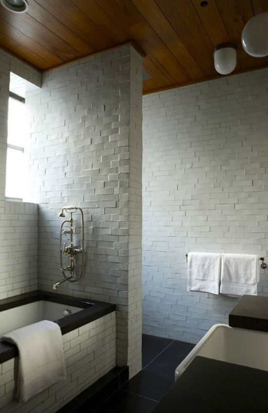 Wooden ceiling and white brick walls in this bathroom designed by Fernando Santangelo via Remodelista.
