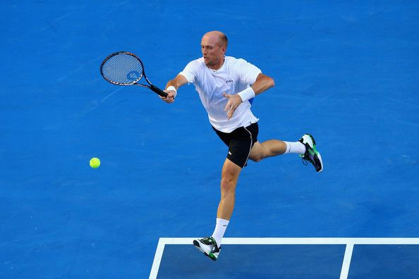 Nikolay Davydenko of Russia plays a forehand in his second round match against Roger Federer of Switzerland during day four of the 2013 Australian Open at Melbourne Park on January 17, 2013 in Melbourne, Australia.