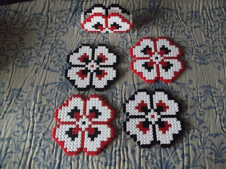 Perfect to save your table from damage, this set of coasters with their own stand will add a bit of originality to your home. Made of fuse beads, each coaster is 9 x 9 cm and this set includes four. Colours can be changed to suit your taste.  The stand where you keep the coasters has to be sh...