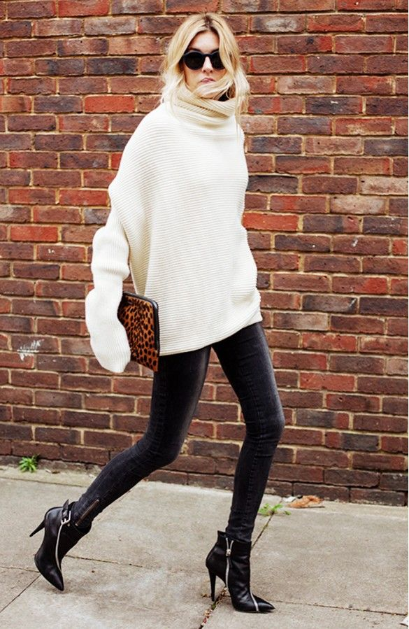 Camille Charriere wears an oversize knit turtleneck in off white, black skinny jeans, ankle boots, an animal print clutch, and round sunglasses