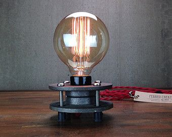 This industrial table lamp can be adjusted to control the height as well as the angle of the shade to place light where you need it most.  A 60 watt filament bulb lights up an 8 inch aged copper shade for a warm ambient glow.  The lamp is constructed from heavy duty industrial piping. The vintage bulbs are easy to replace and can be found at your local hardware store. Power is supplied by an antique style cloth covered cord. The high end antique brass socket features a vintage on/off key...