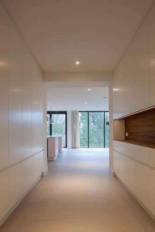ROTTERDAM EN PLEIN AIR: NUOVA PROSPETTIVA Armadi a muro a scomparsa delimitano l'accesso alla cucina, caratterizzato da finiture total-white. Tutti i pavimenti della nuova costruzione sono in cemento rasato.