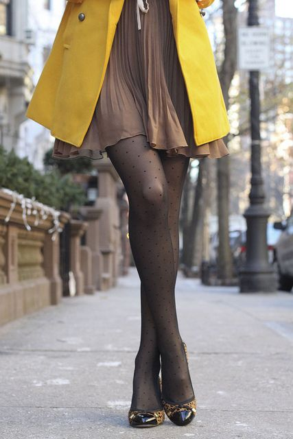 great marigold yellow coat over light brown dress.  (but it looks like she really has to go to the bathroom!)