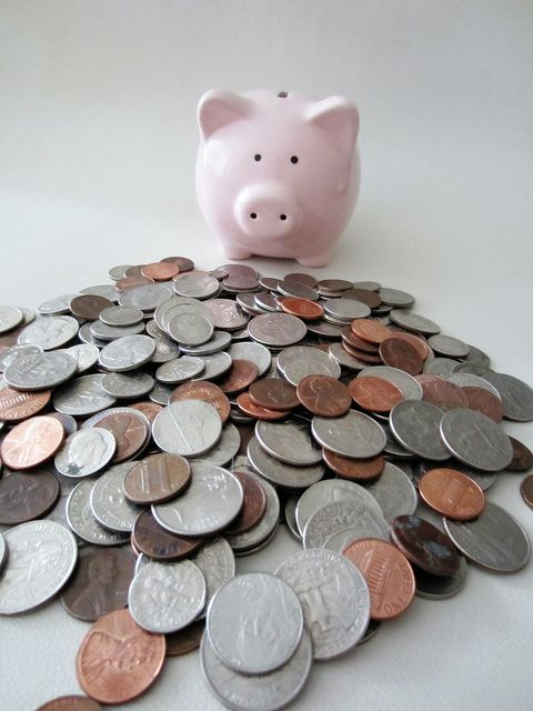 A piggy bank looking at a pile of coins     Piggy banks with your custom imprint for a business or organization